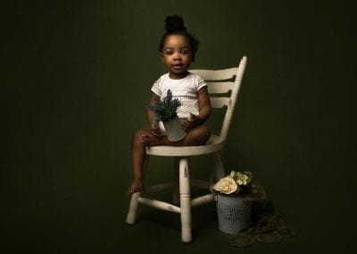 Toddler sitting on a chair holding flowers