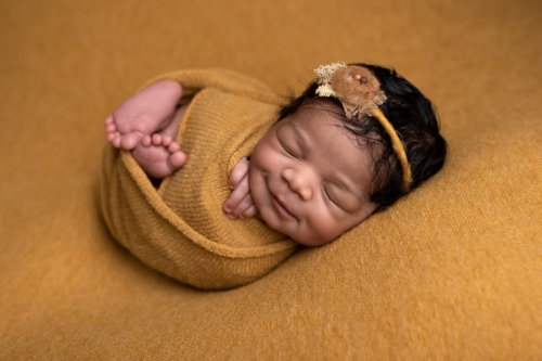 Sleeping Newborn Baby Girl Smilling, Wrapped in Mustard Coloured Wrap
